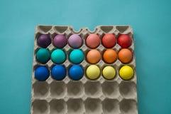 Mão vibrante ovos da páscoa coloridos tingidos em uma caixa de ovo do cartão vista imagem de stock royalty free