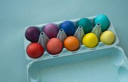 Mão vibrante ovos da páscoa coloridos tingidos em uma caixa de ovo do cartão vista fotografia de stock