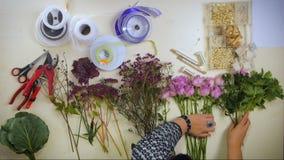 Mãos aéreas de flores de espalhamento de um florista em uma superfície de trabalho video estoque