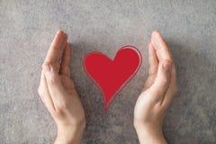 Mãos abertas do homem e coração de proteção Fotografia de Stock Royalty Free