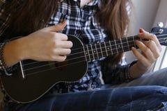 Mãos adolescentes da menina com a guitarra da uquelele na camisa e em calças de brim verificadas Imagem de Stock Royalty Free