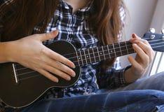 Mãos adolescentes da menina com a guitarra da uquelele na camisa e em calças de brim verificadas Foto de Stock Royalty Free