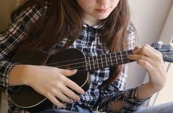 Mãos adolescentes da menina com a guitarra da uquelele na camisa e em calças de brim verificadas Imagens de Stock