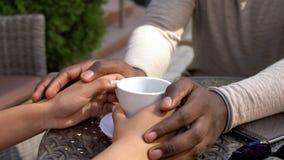 Mãos africanas da amiga da terra arrendada do homem, data romântica no café, expressão do amor fotografia de stock royalty free