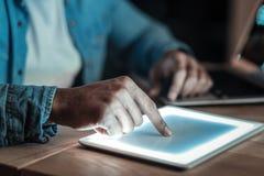 Mãos afro-americanas masculinas que tocam na tela do sensor Imagem de Stock Royalty Free