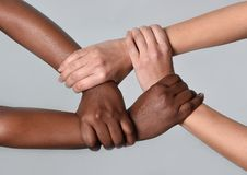 Mãos americanas caucasianos brancas da fêmea e do africano negro que mantêm-se unidas contra o racismo e a xenofobia imagens de stock royalty free