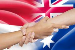 Mãos amiga com as bandeiras indonésias e australianas Imagem de Stock Royalty Free