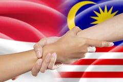 Mãos amiga com as bandeiras indonésias e malaias Fotografia de Stock