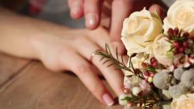 Mãos ao lado do ramalhete do casamento Fotografia de Stock