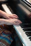 Mãos ascendentes próximas da mulher do vertical em chaves do piano foto de stock