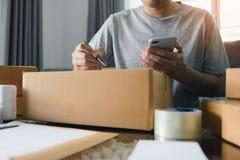 Mãos asiáticas novas do proprietário empresarial do homem que escrevem o endereço na caixa de cartão no local de trabalho ou no e foto de stock royalty free
