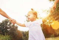 Mãos bonitos da tomada da menina com seus povos dos parentes foto de stock