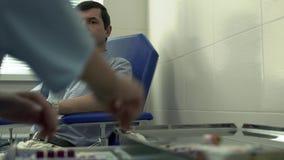 Mãos borradas da enfermeira que prepara-se para tomar o sangue do paciente considerável adulto que senta-se na poltrona no video estoque