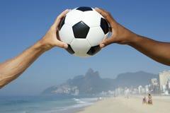Mãos brasileiras que guardam o Rio da bola de futebol do futebol fotos de stock