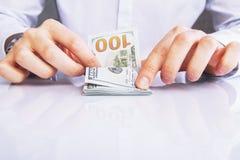 Mãos caucasianos que contam dólares imagem de stock