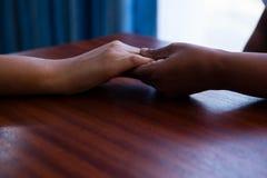 Mãos colhidas da enfermeira que consolam a mulher superior no lar de idosos Fotos de Stock