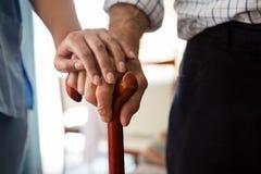Mãos colhidas do doutor fêmea e do homem superior que guardam o bastão de passeio Fotografia de Stock