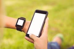 Mãos colhidas que vestem o relógio esperto e que guardam o smartphone imagem de stock royalty free