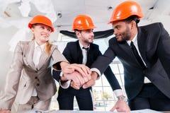 Mãos colocadas arquitetos nas mãos Arquiteto de três businessmеn encontrado Fotografia de Stock