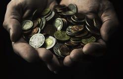 Mãos colocadas completamente das moedas em um fundo escuro foto de stock