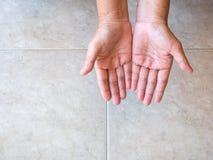 Mãos colocadas da mulher adulta no fundo da telha Fotos de Stock Royalty Free