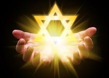 Mãos colocadas e que guardam ou que mostram a estrela de David Magen David ou selo de Solomon imagem de stock