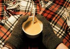 Mãos colocadas gloved do dedo em torno de uma caneca enchida com o café e o leite fotos de stock