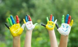 Mãos coloridas com o sorriso pintado em pinturas coloridas fotografia de stock