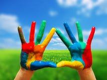 Mãos coloridas pintadas que mostram a maneira de cancelar a vida feliz Fotografia de Stock Royalty Free