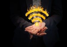 mãos com ícone do fogo de WIFI no meio Fundo preto Fotografia de Stock Royalty Free