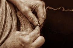 Mãos com agulhas de confecção de malhas perto no estilo retro Fotos de Stock