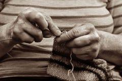 Mãos com agulhas de confecção de malhas perto no estilo retro Foto de Stock Royalty Free