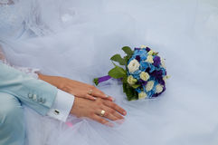 Mãos com alianças de casamento e ramalhete do casamento Imagem de Stock Royalty Free