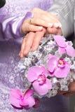 Mãos com alianças de casamento e ramalhete do fower Fotografia de Stock
