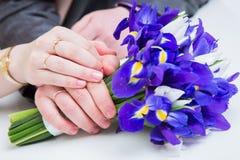Mãos com alianças de casamento e ramalhete do fower Imagens de Stock Royalty Free
