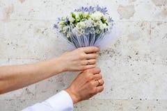 Mãos com alianças de casamento no ramalhete nupcial Fotos de Stock