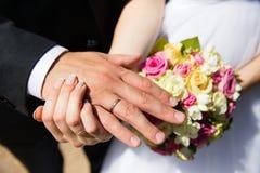 Mãos com alianças de casamento no ramalhete nupcial Foto de Stock