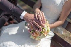 Mãos com alianças de casamento no ramalhete nupcial foto de stock royalty free