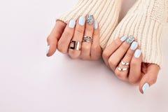 Mãos com anéis prateados e tratamento de mãos azul Imagem de Stock