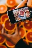Mãos com as imagens do close-up do telefone do alimento Lote da toranja imagem de stock