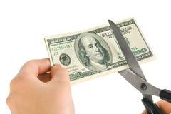 Mãos com as tesouras que cortam o dinheiro Fotografia de Stock