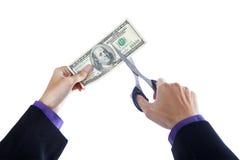 Mãos com as tesouras que cortam o dinheiro Fotos de Stock
