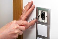 Mãos com a chave de fenda que repara um interruptor Fotografia de Stock Royalty Free