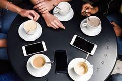 Mãos com copos de café e smartphones em um café urbano Fotografia de Stock Royalty Free
