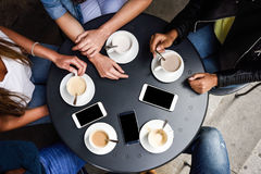 Mãos com copos de café e smartphones em um café urbano Imagens de Stock