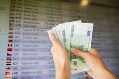 Mãos com euro- dinheiro sobre taxas de câmbio da moeda Fotografia de Stock Royalty Free