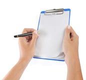 Mãos com a folha de papel na prancheta Foto de Stock