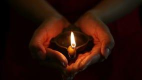 Mãos com a lâmpada de óleo de Diwali