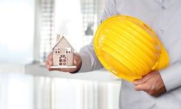 Mãos com o capacete da casa e do trabalho, concep da segurança e da construção Foto de Stock