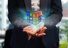 mãos com o cubo de ícones da aplicação com luzes azuis Fotos de Stock Royalty Free